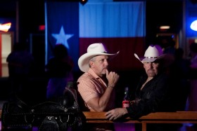 "Rick Threadgill, left, and Scott Traugher people watch at the Neon Boots Dancehall and Saloon, a country-style gay, lesbian and transgender bar located in the former home of the Esquire Ballroom  at 11410 Hempstead Highway Thursday, Aug. 15, 2013, in Houston.  The Esquire has gone through many transitions. It began as a plaice where Willie Nelson played a regular gig and wrote the song ""Night Life"" about the place. Patsy Cline used to sing there too. The hall eventually evolved into Latin dance clubs and now has gone back to its country roots. ( Johnny Hanson / Houston Chronicle )"